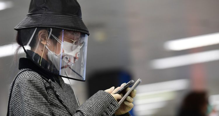A passenger wearing a protective mask and a plastic face shield checks her smartphone as she waits to check in at Milan's Linate airport on March 11, 2020, a day after Italy imposed unprecedented national restrictions on its 60 million people Tuesday to control the deadly COVID-19 coronavirus. (Photo by Miguel MEDINA / AFP)